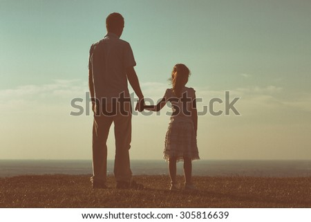 Father and daughter enjoy watching sunset together.Precious family moments Image is intentionally with grain and toned. - stock photo