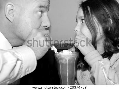 Father and daughter enjoying ice cream shake - stock photo