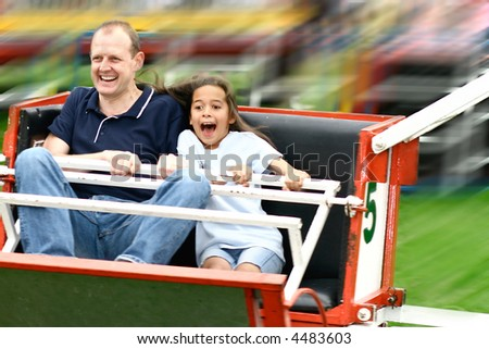 Father and daughter enjoying the fast octopus ride at the amusement fair in the park. - stock photo