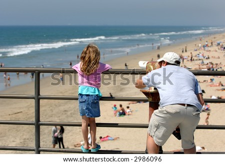 Father and Daughter Examine Coast Through Telescope - stock photo