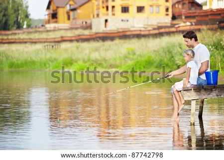 Father and daughter fishing - stock photo