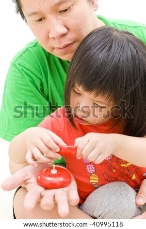 father and daughter fixing spoilt yoyo - stock photo