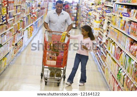 Father and daughter grocery shopping in supermarket - stock photo