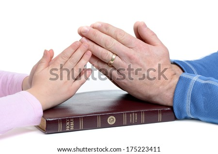 father and daughter hands in prayer over bible white background - stock photo