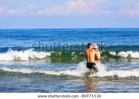 Father and daughter have fun on the beach - stock photo