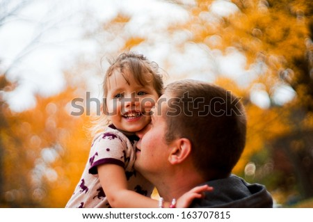 Father and daughter having fun in the autumn colorful forest - stock photo