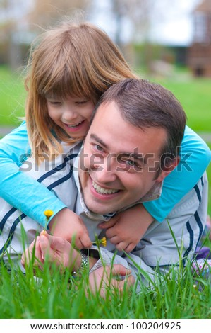Father and daughter having fun in the grass on beautiful spring day. - stock photo