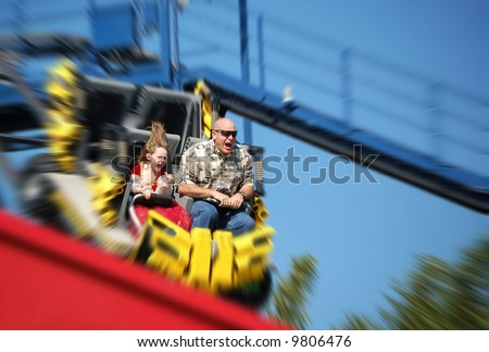 Father and daughter having fun on rollercoaster - stock photo