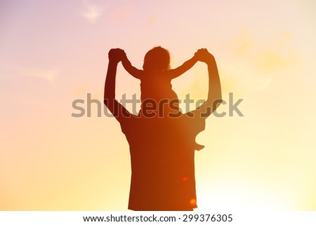father and daughter having fun on sunset sky - stock photo