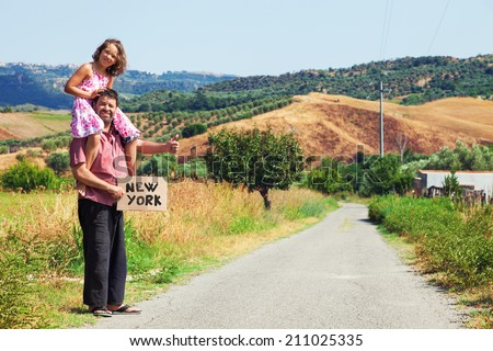 father and daughter hitchhiking along a road - stock photo