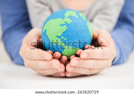 father and daughter holding earth clay globe - stock photo