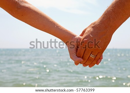 Father and daughter holding hands near the beach