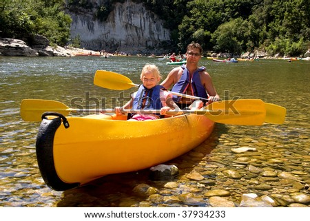 Father and daughter in canoe enjoying the holidays - stock photo