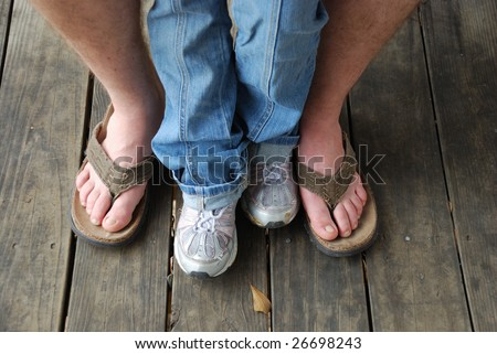 Father and daughter in sandals and sneakers sitting - stock photo