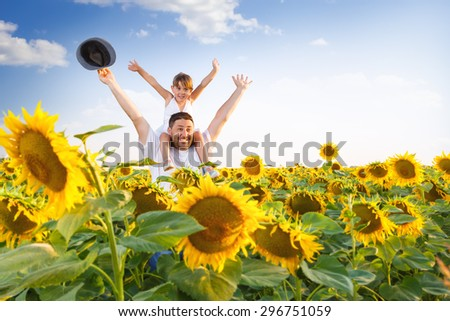Father and daughter in sunflower field with their hands raised - stock photo