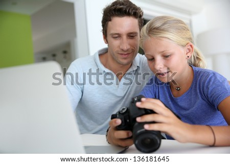 Father and daughter looking at digital camera and laptop - stock photo