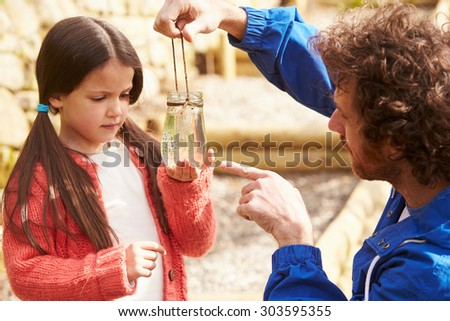 Father And Daughter Looking At Frogspawn In Jar - stock photo
