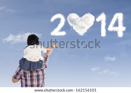 Father and daughter looking at shaped clouds of 2014 under blue sky - stock photo