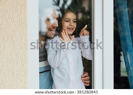 father and daughter looking out the window and smiling - stock photo