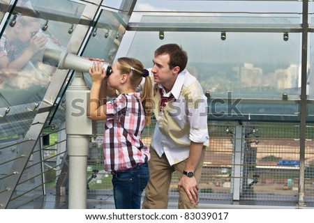 Father and daughter looking through tourist telescope , exploring landscape. - stock photo