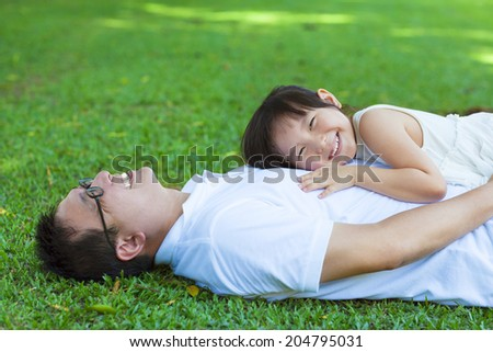 father and daughter lying on a meadow in the park - stock photo