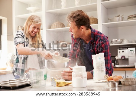 Father and daughter making a cake together - stock photo