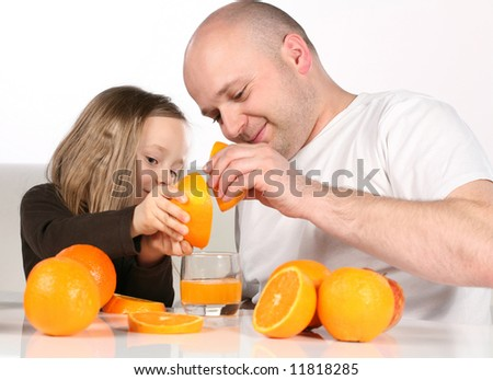 Father and daughter making a fresh organic orange juice together. Studio shot on white.