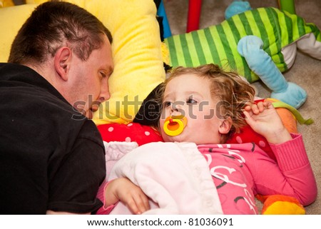 Father and daughter napping on the floor. - stock photo