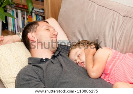 Father and daughter napping on the sofa.