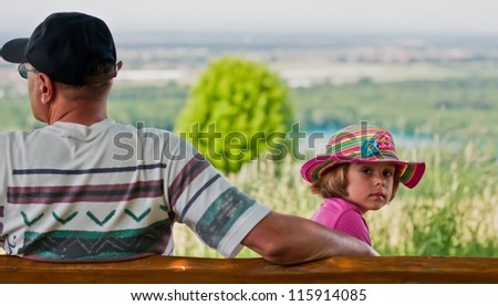 Father and daughter on a bench - stock photo