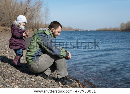 Father and daughter on a river bank