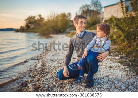 Father and daughter on a walk at sunset near the lake