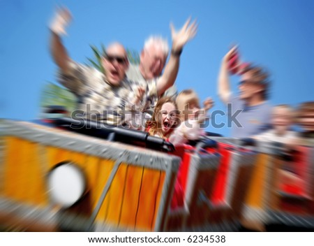 Father and Daughter On Amusement Park Roller Coaster with Zoom Blur - stock photo