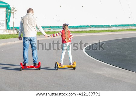 Father and daughter on shoulders riding on modern red and yellow electric mini hover board scooters - stock photo