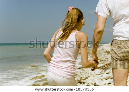 father and daughter on the beach - stock photo