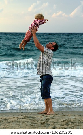 father and daughter on the beach at sunset