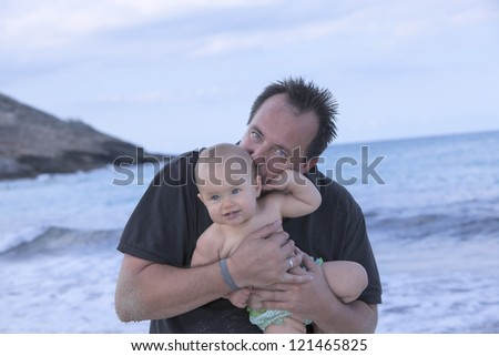 father and daughter on the beach during vacation . father holding and kissing his daughter. - stock photo