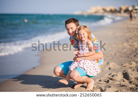 Father and daughter on the beach near the sea. Young man hugs little baby girl