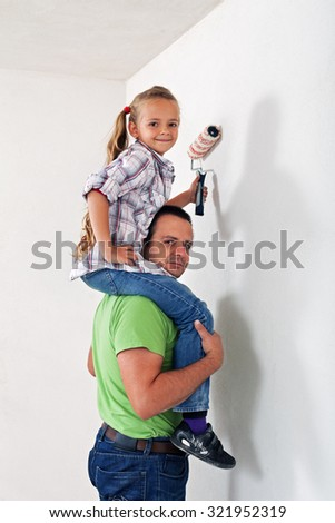 Father and daughter painting the room together - having fun together - stock photo