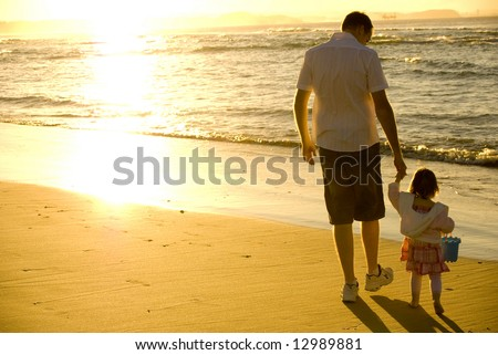 Father and Daughter playing at the beach - stock photo