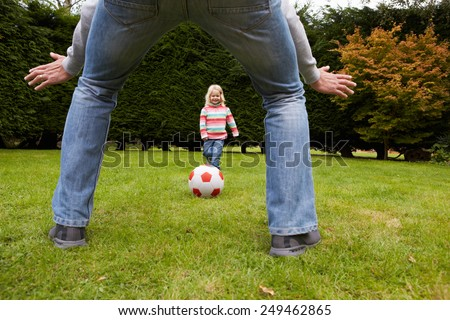 Father And Daughter Playing Football In Garden Together - stock photo
