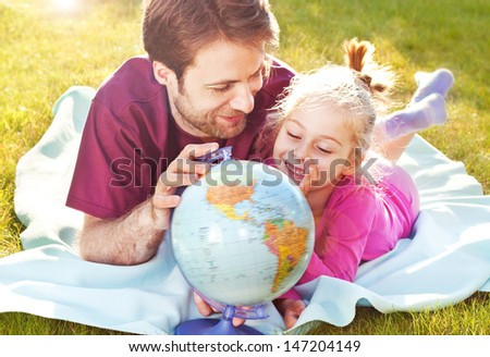 Father and daughter playing globe while laying outdoor on the grass in the garden during sunset - stock photo