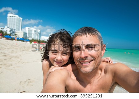 Father and daughter playing happy at a beautiful beach making selfie.