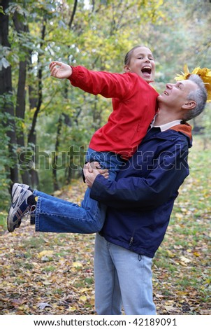 Father and daughter playing in autumn park - stock photo