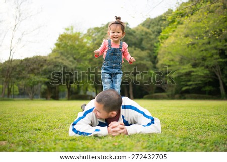 Father and daughter playing in the lawn - stock photo