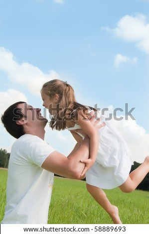 Father and daughter playing in the meadow - stock photo