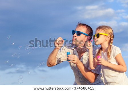 Father and daughter playing in the park  at the day time. Concept of friendly family. Picture made on the background of blue sky. - stock photo