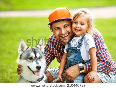 father and  daughter playing in the park in love with Dog Husky - stock photo