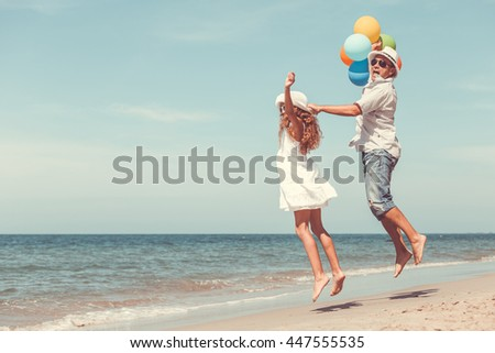 Father and daughter playing on the beach at the day time. People having fun on the nature. Concept of friendly family. - stock photo