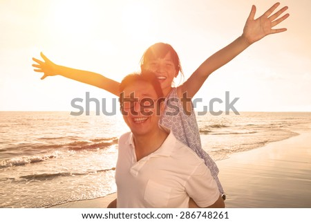 Father and daughter playing on the beach at the sunset - stock photo